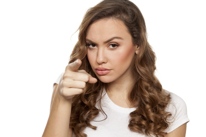 angry beautiful girl pointing a finger at you on a white background